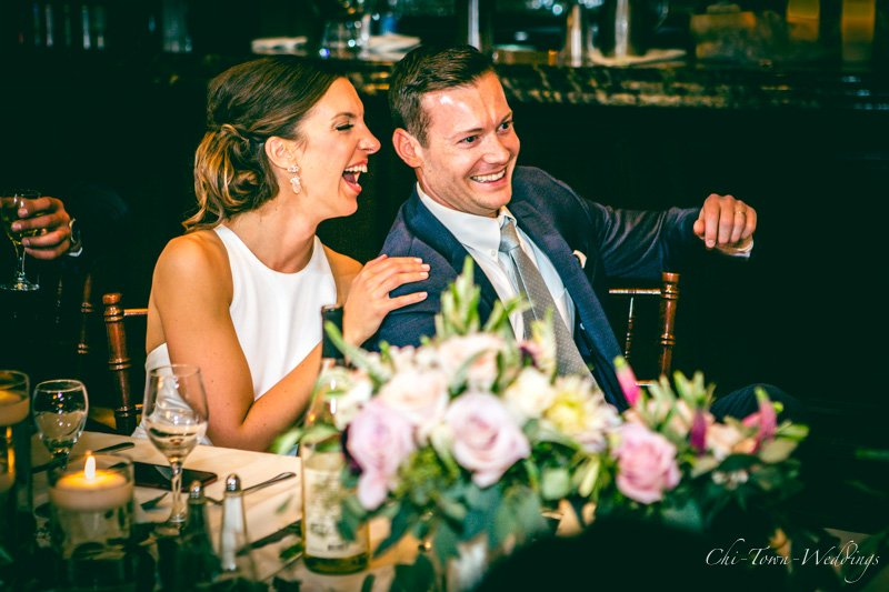 Bride and Groom Candidly laughing during speech