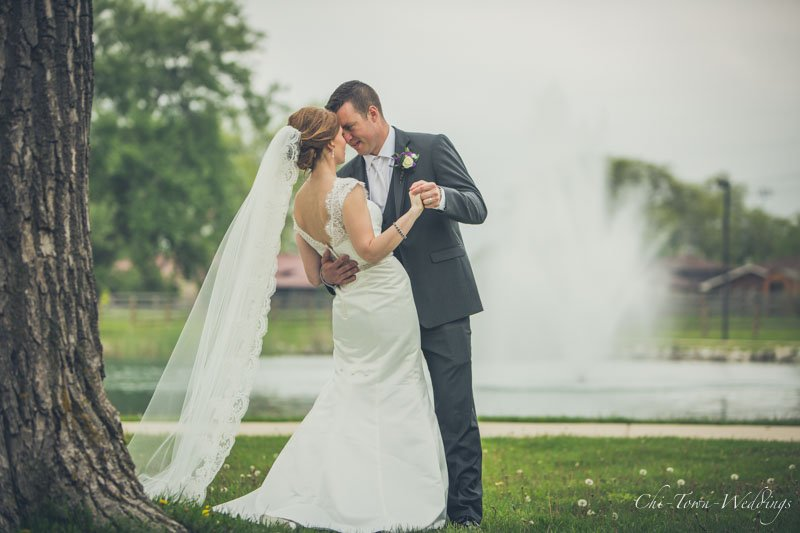 Bride and Groom posing in-front of weather fountain on the grass