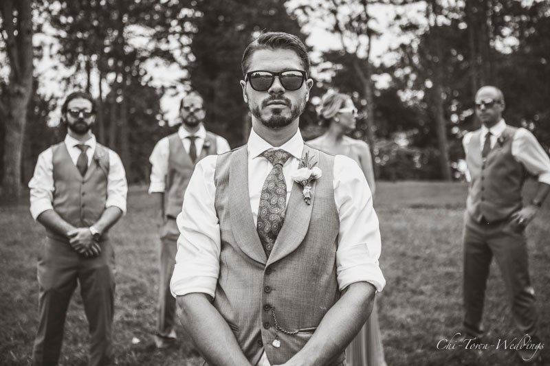 Groomsmen wearing glasses posing looking cool sepia tone