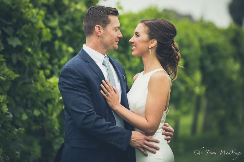 Bride and Groom posing in a vineyard
