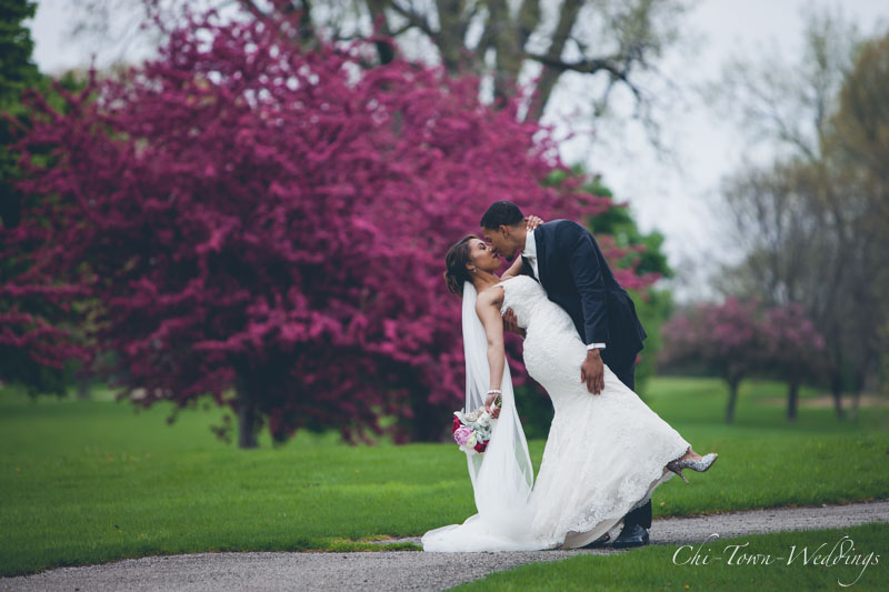 Bride and Groom posing after wedding with Spring color trees in background